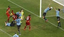 La selección de Uruguay se impuso el viernes a la de Ghana en la tanda de penaltis, en un partido de cuartos de final del Mundial 2010 que terminó 1-1 al final de la prórroga. En la imagen, el uruguayo Luis Suárez (D) para el balón con la mano durante un partido de cuartos de final del Mundial 2010 disputado ante Ghana en el estadio Soccer City de Johannesburgo, el 2 de julio de 2010. REUTERS/Brian Snyder